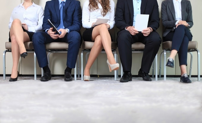 job candidates sitting in a row of five waiting for their interview for a new job