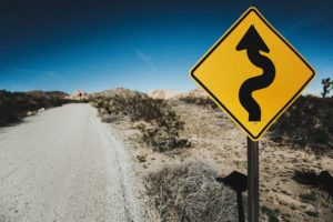 A yellow roadside sign describes the upcoming twists and turns in the road