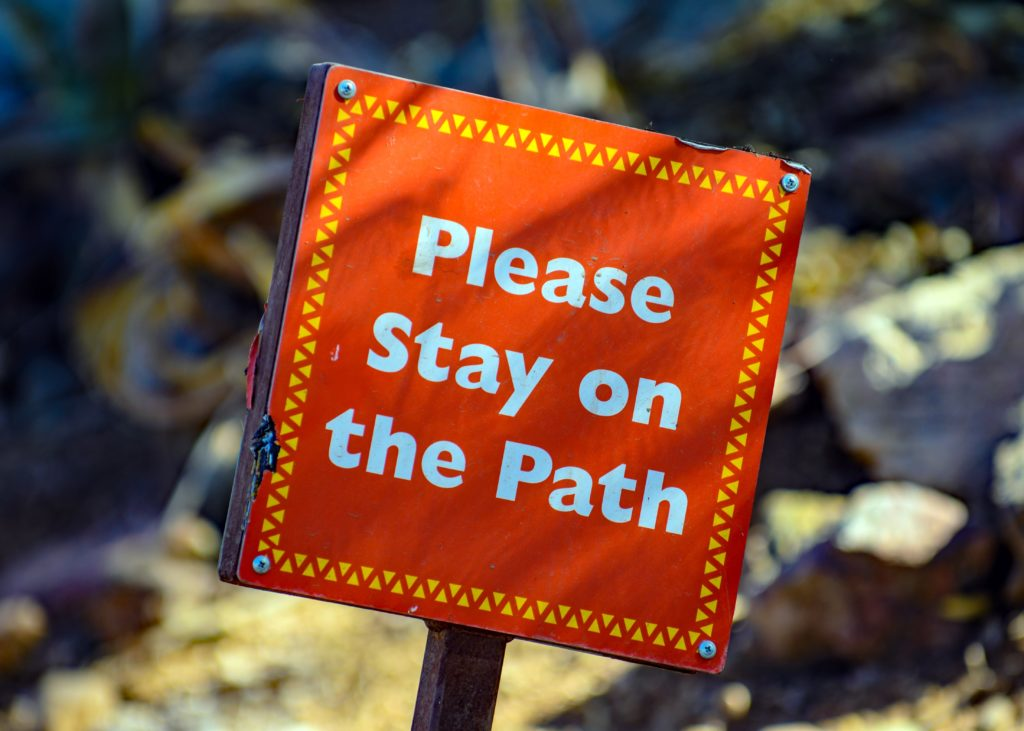 """An orange sign with a yellow border reads """"Please Stay on the Path"""" in white letters"""